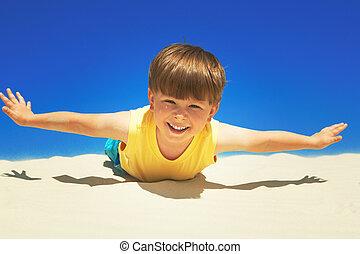 Joyful boy stretching his hands and lying sand