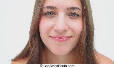 Joyful brunette applying mascara on her eyelashes against a...