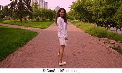 joyful brunette stroll in city - back view young woman in ...