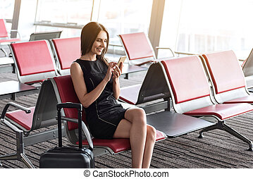 Joyful business lady is using her mobile phone