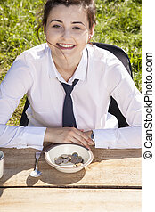 Joyful business woman sitting in front of a plate with money