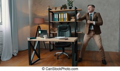 Joyful businessman in a suit is dancing in the office. Business success.