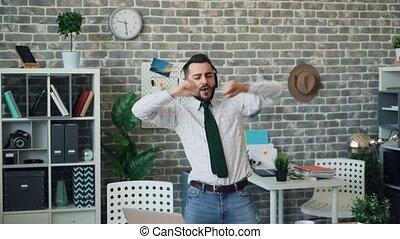 Joyful businessman listening to music dancing singing having fun in office
