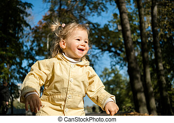 Joyful Caucasian child girl in an autumn jacket walks in the forest