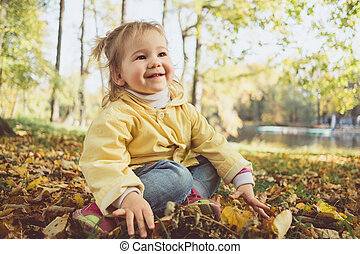 Joyful Caucasian child girl in autumn sits on leaves in the park