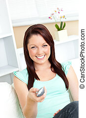Joyful caucasian woman holding a remote smiling at the camera