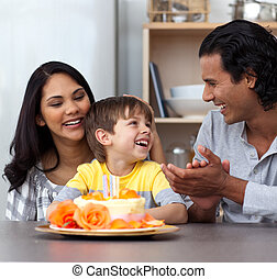 Joyful child celebrating his birthday with his parents