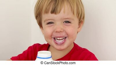 Joyful child drinking yogurt - Messy toddler smiling and...