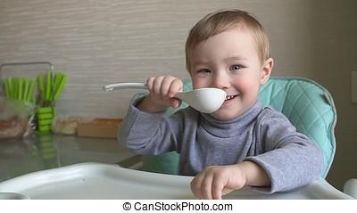 Joyful child eats porridge.