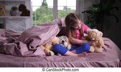 Joyful child hiding under blanket with puppy pet - Cute...