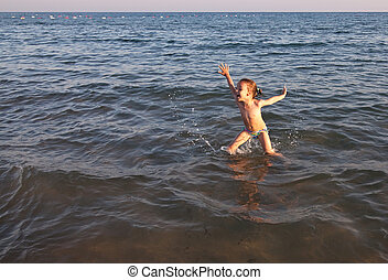 Joyful child jumps out of the sea.