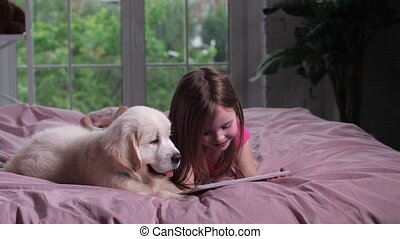 Joyful child watching youtube on tablet with puppy -...