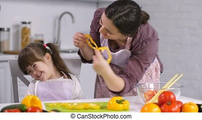 Positive carefree mother and her joyful smiling little daughter with down syndrome having fun while preparing food together. Loving mom playing with her special needs girl in kitchen during cooking.