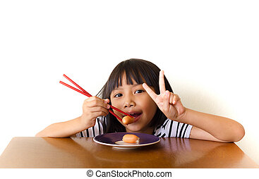 Joyful children girl with red chopsticks sitting at the table