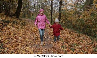 Joyful children running through autumn woodland