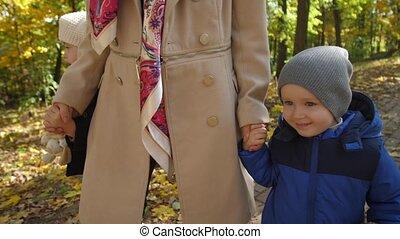 Joyful children walking with mother in autumn park