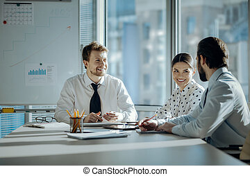 Joyful colleagues chatting cheerfully during meeting