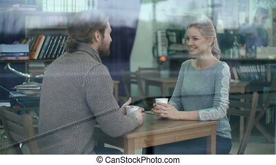 Joyful Communication - Through the cafe window shot of two...