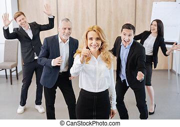 Joyful confident woman standing in front of her colleagues