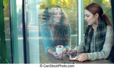 Joyful Conversation - Through the window of cafe shot of two...