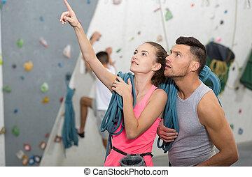 joyful couple climbing up the wall together