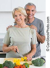 Joyful couple cutting a pepper