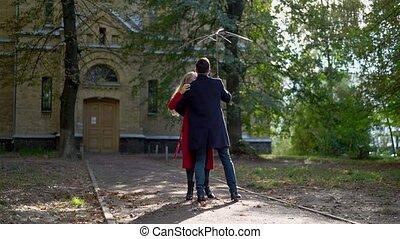 Joyful couple dancing under broken umbrella - Charming...