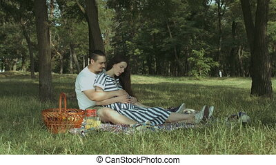 Joyful couple expecting baby picnicking in park