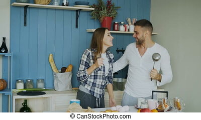 Joyful couple have fun dancing and singing in the kitchen at home in the morning