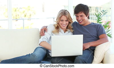 Joyful couple looking at a laptop