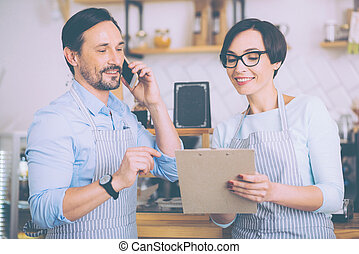 Joyful couple of cafe owners talkign on smart phone