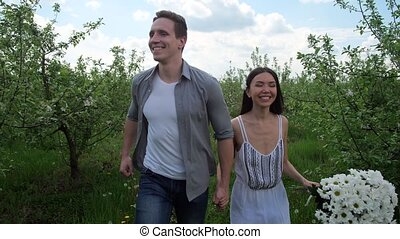 Joyful couple running hand in hand among trees