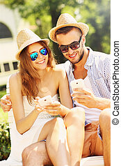 Joyful couple sitting on a bench with smartphones