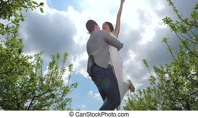 Joyful couple spending leisure in spring orchard - Low angle...