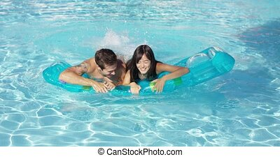 Pair of joyful male and female adults swimming together on inflatable floating plastic mattress in outdoor pool