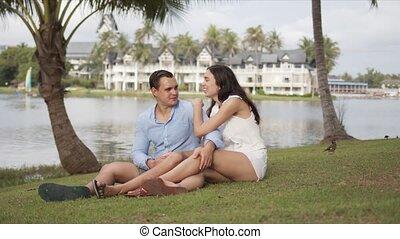 Joyful couple tourists spending time on lawn - Pleased male ...