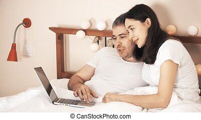 Joyful couple using their laptop in bed at home