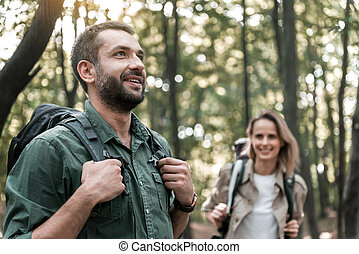 Joyful couple walking in the woods with enjoyment