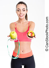 Joyful cute fitness woman making decision between apple and cake
