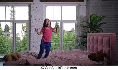 Joyful cute little girl jumping on bed in nursery - Happy...
