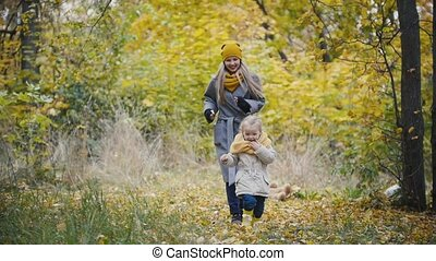 Joyful cute young girl - little daughter laughs and plays catch-up with the mother in autumn park, slow motion