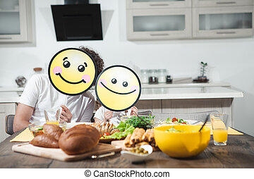 Joyful dad and child eating together in kitchen