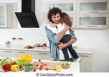 Joyful dad embracing his child in cook room