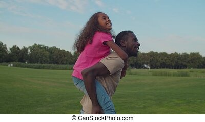 Joyful dad piggybacking excited daughter in nature - Joyful ...