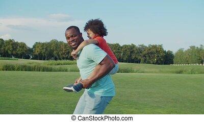 Joyful dad piggybacking excited son in nature
