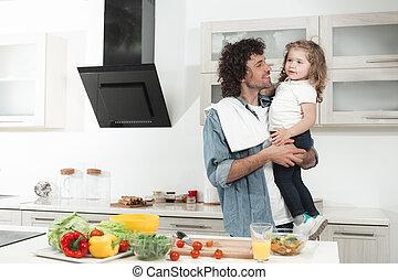 Joyful daddy holding little girl in kitchen