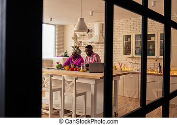 Joyful delighted couple being engaged in cooking