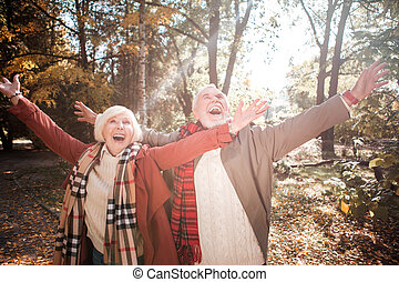 Joyful delighted couple having fun in the forest
