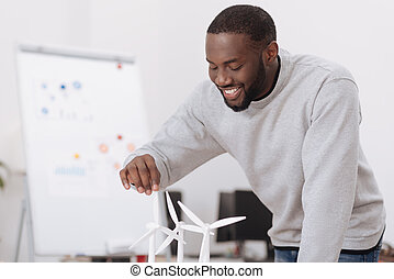 Joyful delighted man looking at the windmill models - Save...