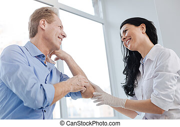 Joyful dermatologist enjoying conversation with patient in the hospital